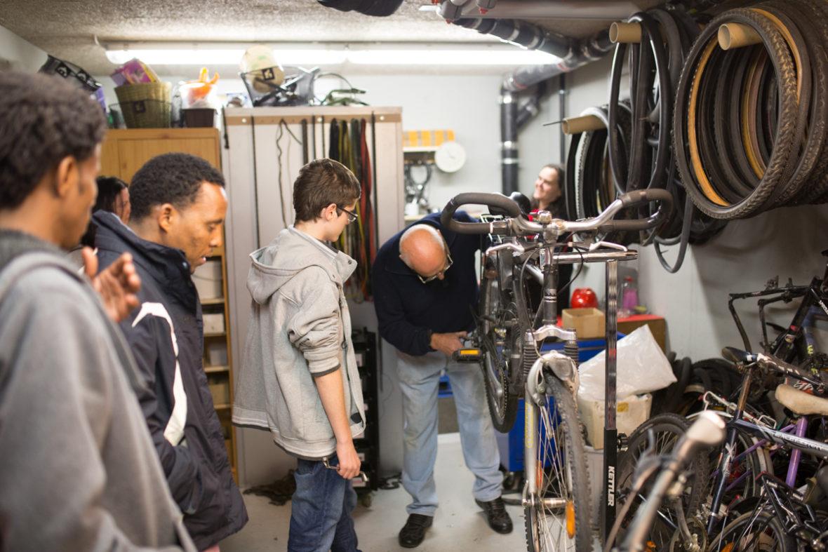 Peschke und Huber reparieren ein Rad. Ein paar Flüchtlinge sehen ihnen dabei zu.