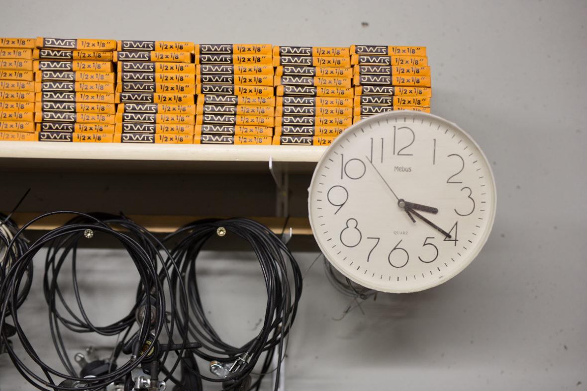 Auf einem Regal in Peschkes Werkstatt stapeln sich feinsäuberlich Kartons mit Schläuchen. Am Regal ist eine große, weiße Uhr befestigt.