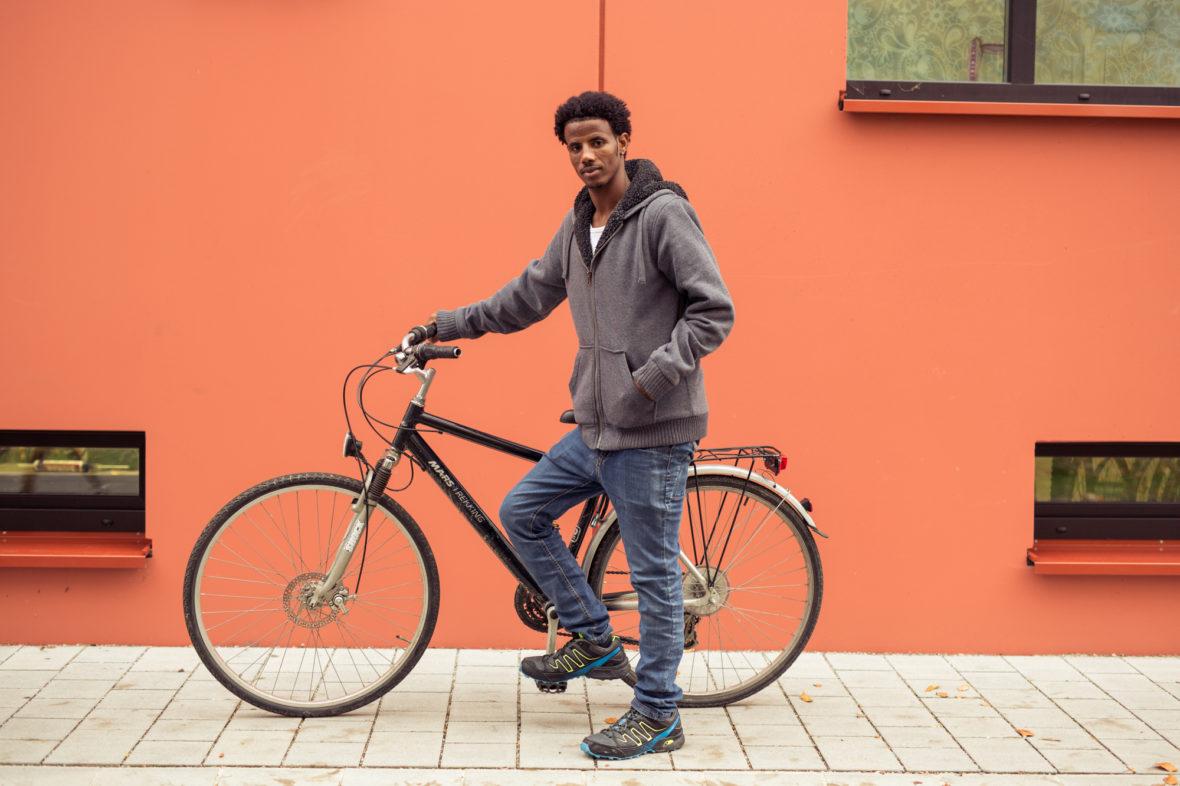 Adhanom zeigt stolz sein repariertes Fahrrad.