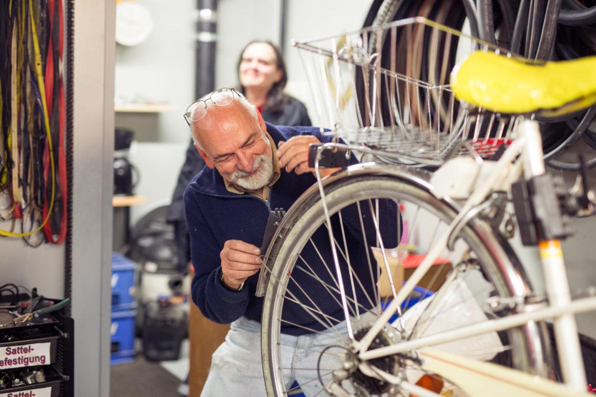 Johann Peschke repariert das Rücklicht eines Fahrrads.