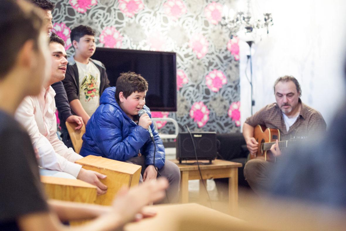 Ein Junge singt ins Mikrofon, während mehrere andere Jungs zum Gitarrenspiel des Sozialarbeiters trommeln.