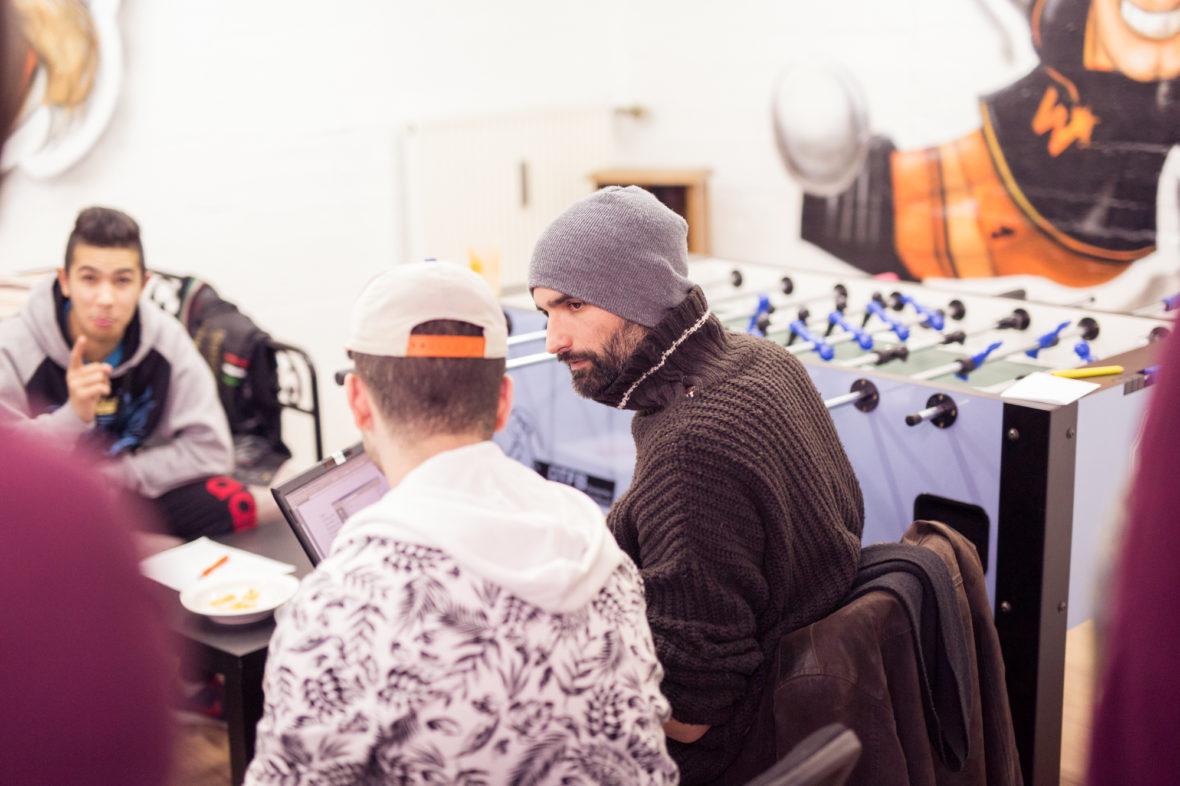 Ein paar Jungs sitzen um einen Laptop und schreiben am Text für ein Hip-Hop Lied.