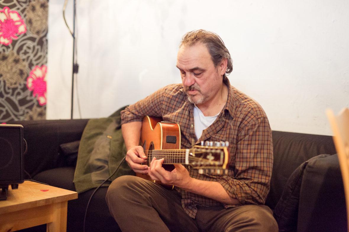 Ein Sozialarbeiter sitzt auf dem Sofa und stimmt seine Gitarre.