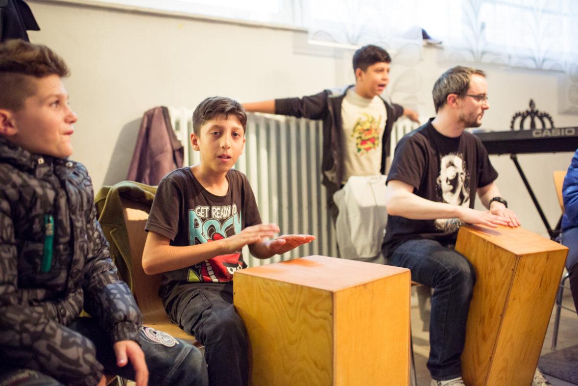 Ein paar Jungs trommeln gemeinsam mit einem Sozialarbeiter auf speziellen Holzkisten.