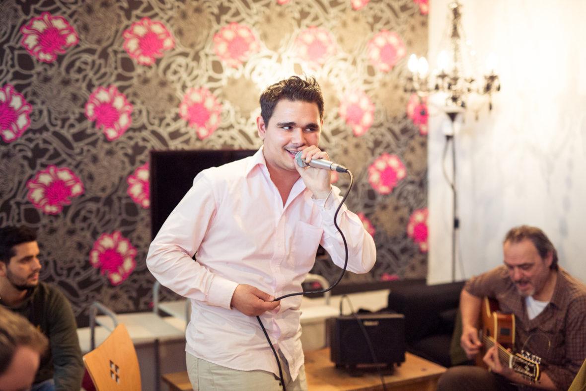 Während ein Sozialarbeiter Gitarre spielt, singt ein Jugendlicher dazu.