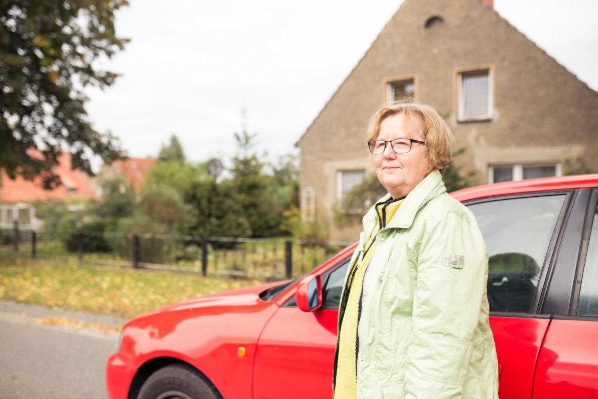 Porträt von Schulz vor ihrem roten Audi. Sie blickt in die Ferne.