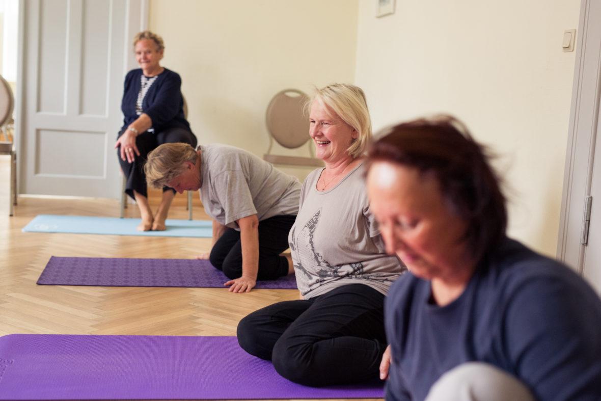 Die Seniorinnen sitzen auf ihren Yogamatten.