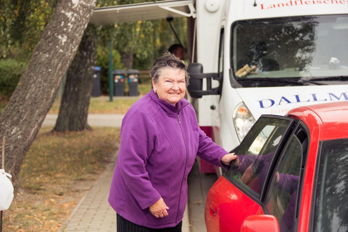 Eine Seniorin öffnet die hintere Tür von Schulz rotem Audi.