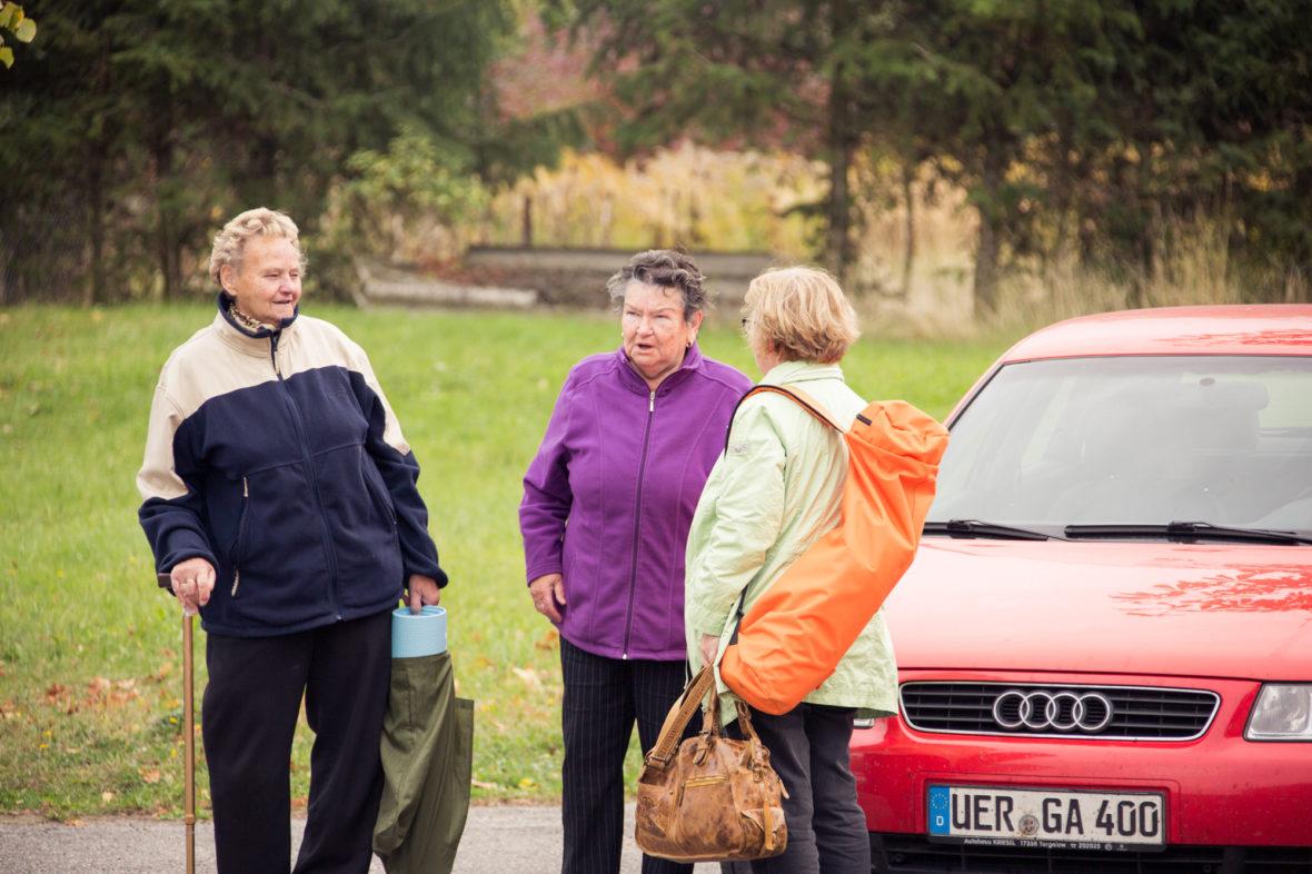 Schulz im Gespräch mit zwei Seniorinnen. Alle drei haben eine Yoga-Matte bei sich.