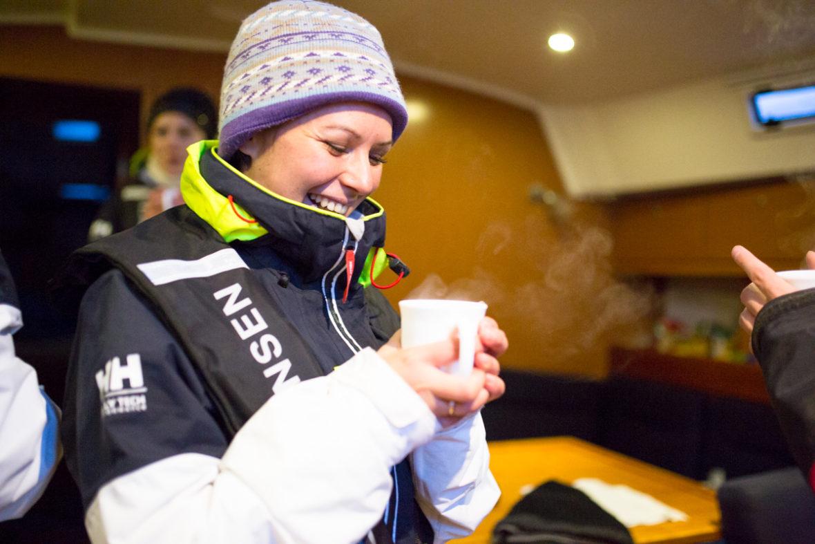 Eine Segelrebellin trinkt Tee unter Deck. Aus der Tasse in ihren Händen dampft es.