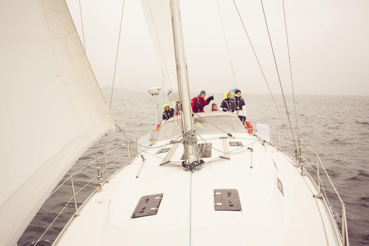 Die Segelrebellen auf dem offenen Meer. Der Schiffsführer zeigt auf etwas in der Ferne, die anderen blicken in die Richtung, in die sein Finger zeigt.