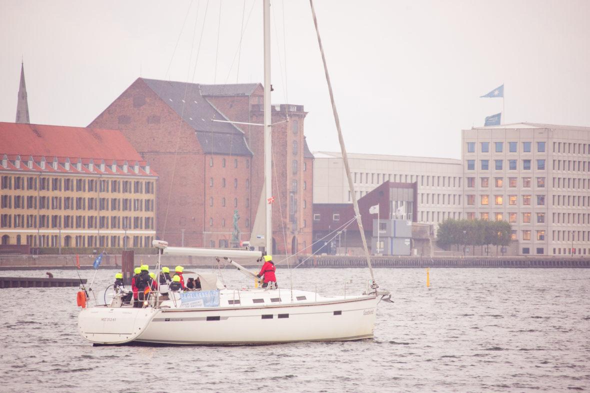 Der Blick vom Hafen auf das Segelschiff: Die Segelrebellen sind an Deck und tragen neongelbe Mützen, im Hintergrund Kopenhagen.