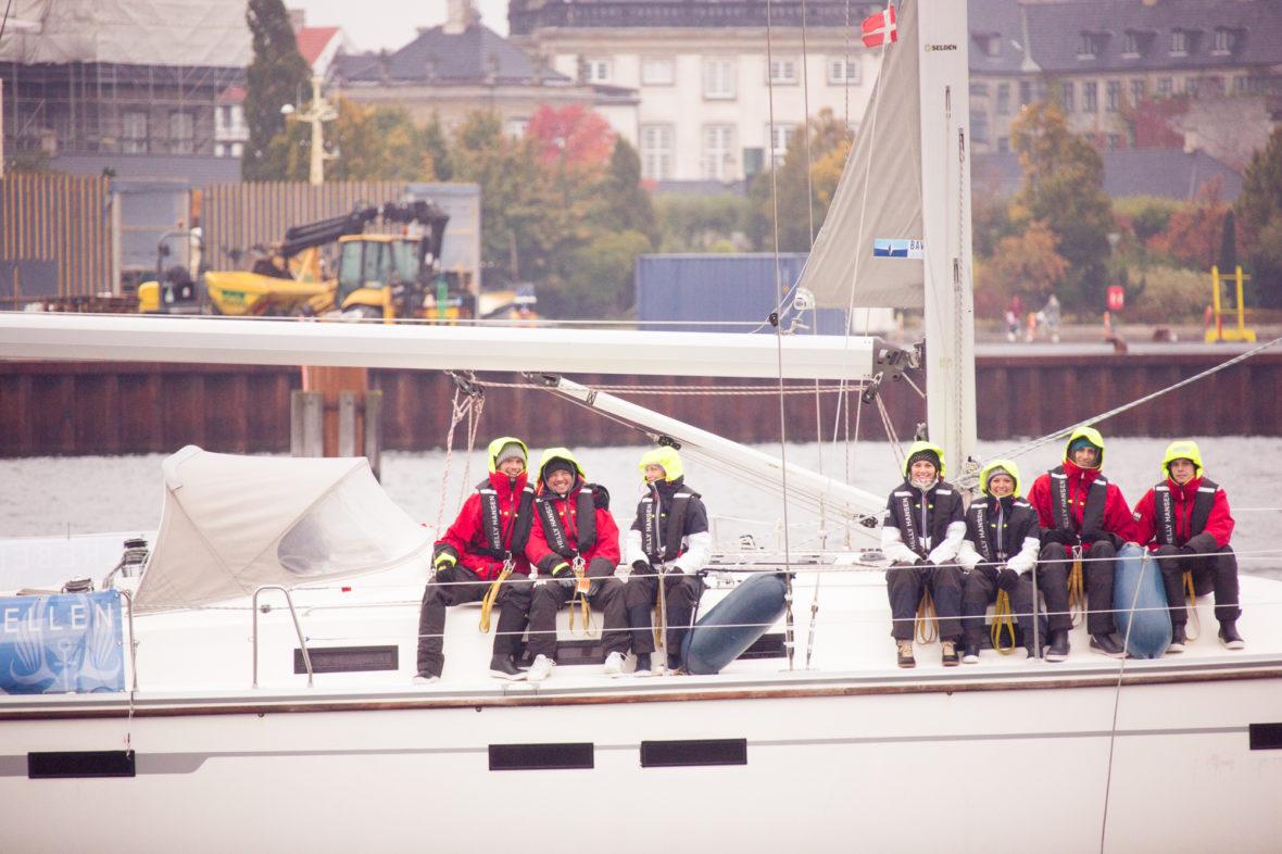 Im Hafen von Kopenhagen: In dicken Jacken und mit Mützen sitzt die Crew an Deck und lacht in die Kamera.