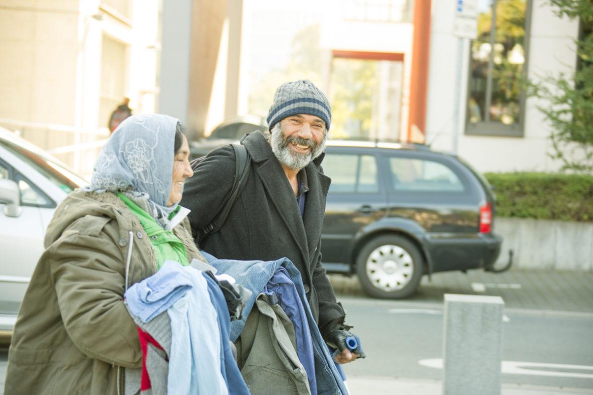 Ein obdachloses Pärchen verlässt den Platz. Sie trägt mehrere Kleidungsstücke auf den Armen, er lacht in die Kamera.