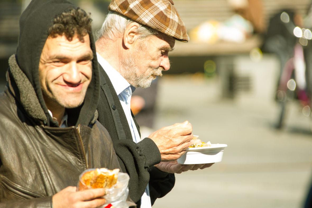 Zwei obdachlose Männer essen gemeinsam, einer lächelt in die Kamera.