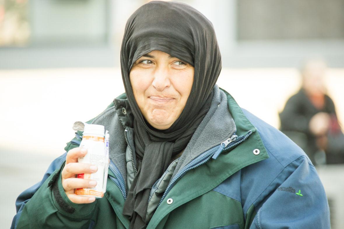 Eine obdachlose Frau trinkt ein Joghurtgetränk.
