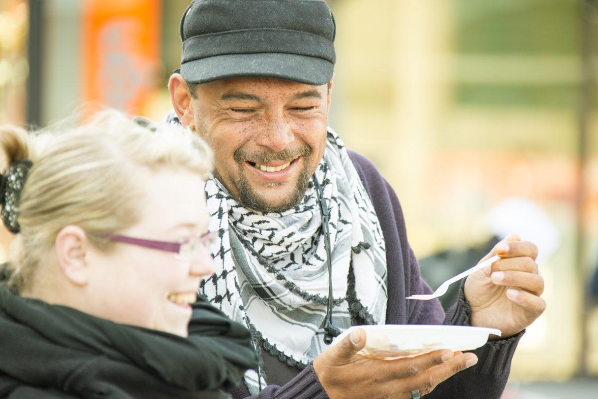 Während ein obdachloser Mann eine warme Mahlzeit zu sich nimmt, unterhält er sich mit einer Helferin. Beide lachen.