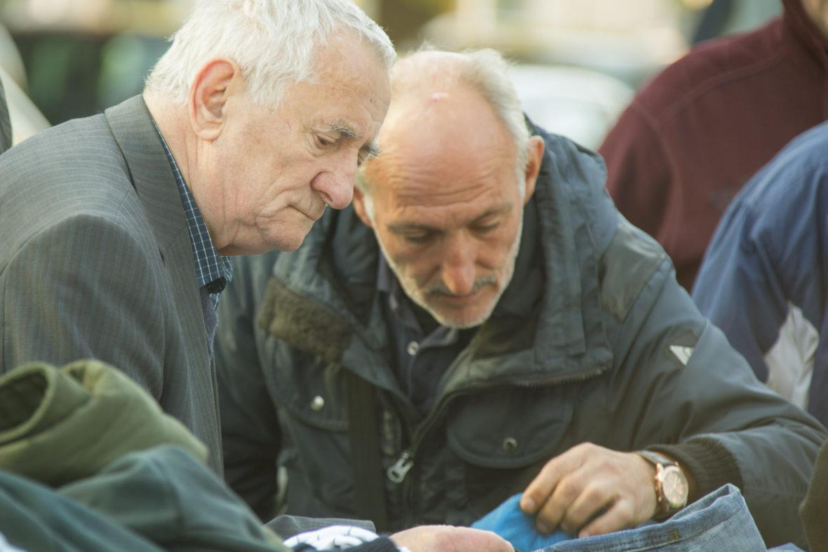 Zwei obdachlose Männer suchen sich Kleidungsstücke aus.