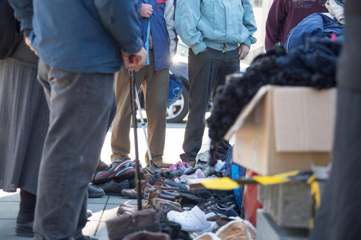 Gespendete Schuhpaare stehen auf dem Boden, ein Karton ist bis über den Rand voll mit Kleidung.