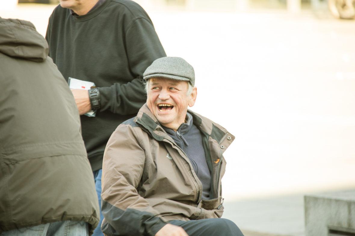 Porträt eines lachenden obdachlosen Mannes.