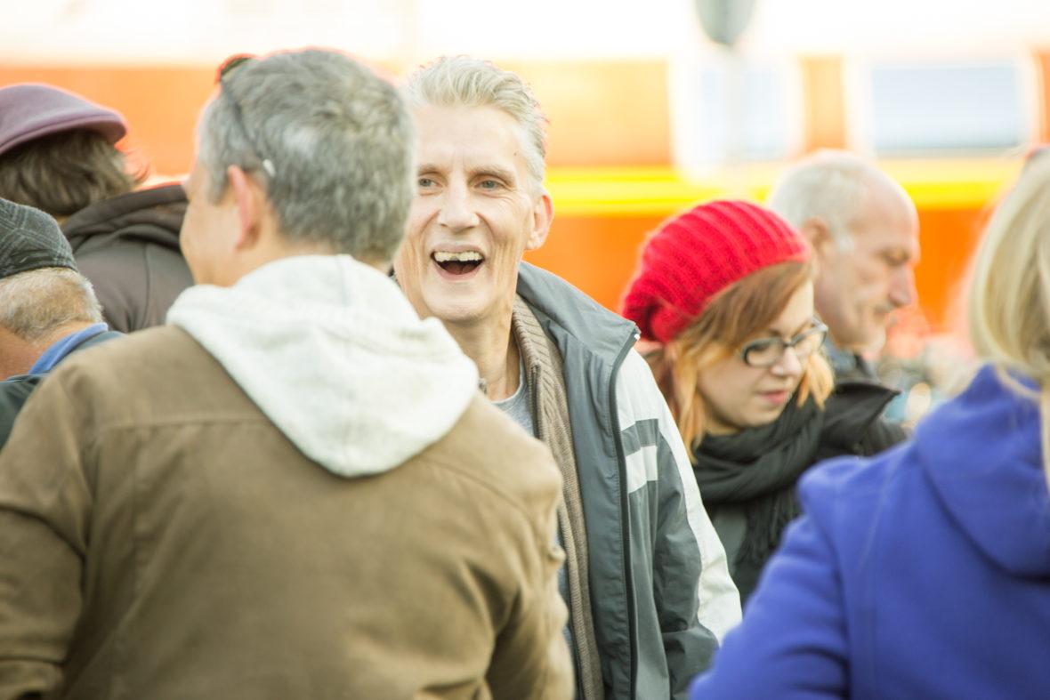 Ein obdachloser Mann lacht im Gespräch mit einem anderen.
