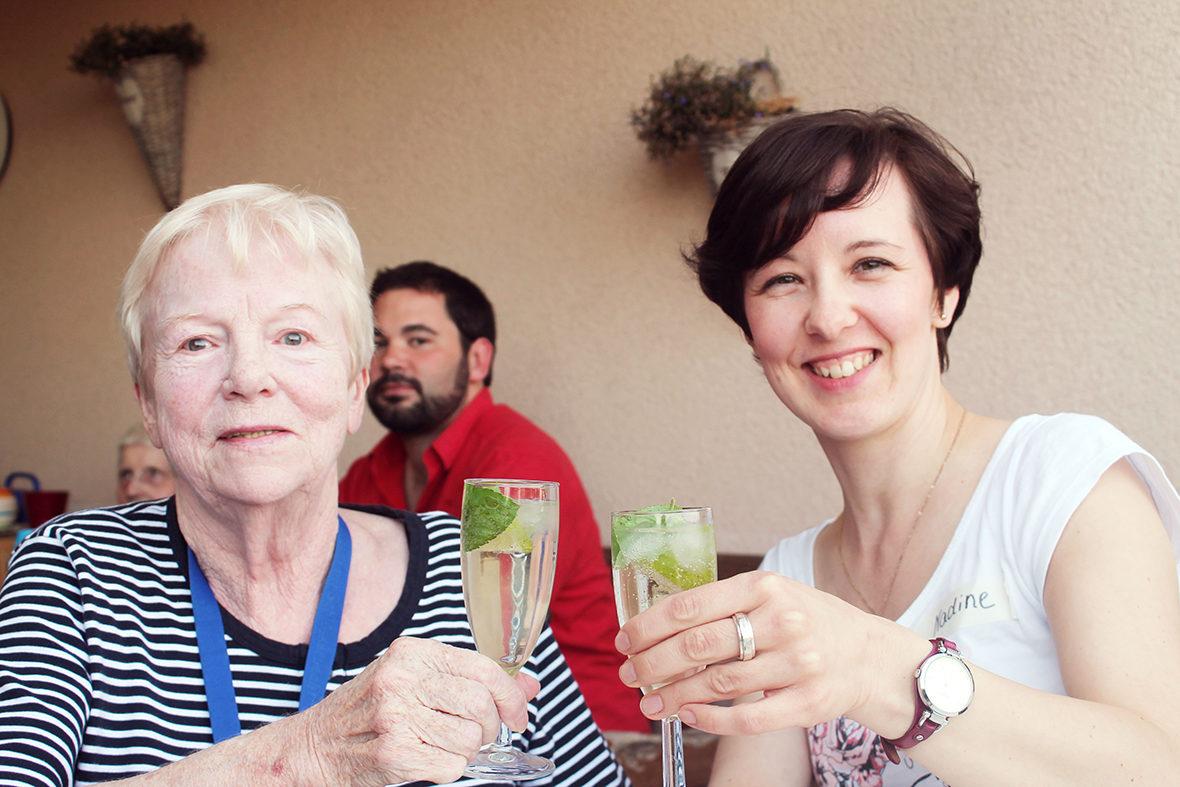 Ein Tandempaar stößt mit einem Glas Hugo an.