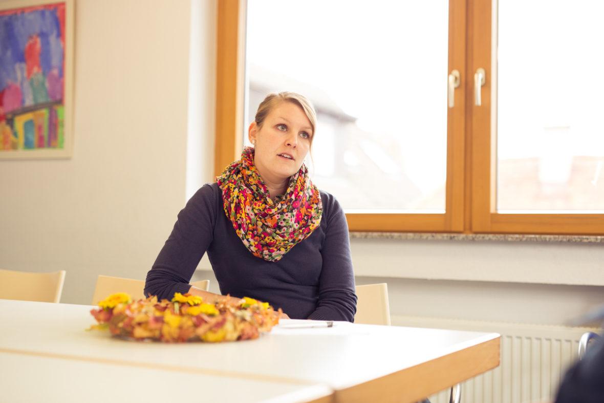 Gruppenleiterin Isabelle Forstner sitzt am Tisch in dem Raum, in dem die Gesprächsgruppe sich wöchentlich trifft.