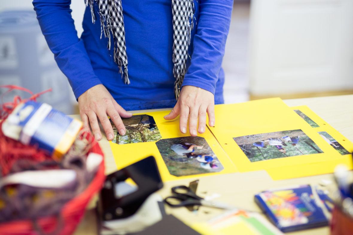Eine Mutter positioniert Bilder auf gelbem Tonpapier.