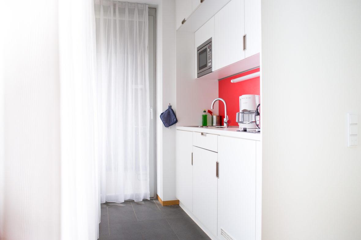 Die weiße Küchenzeile hat eine rote Wand.