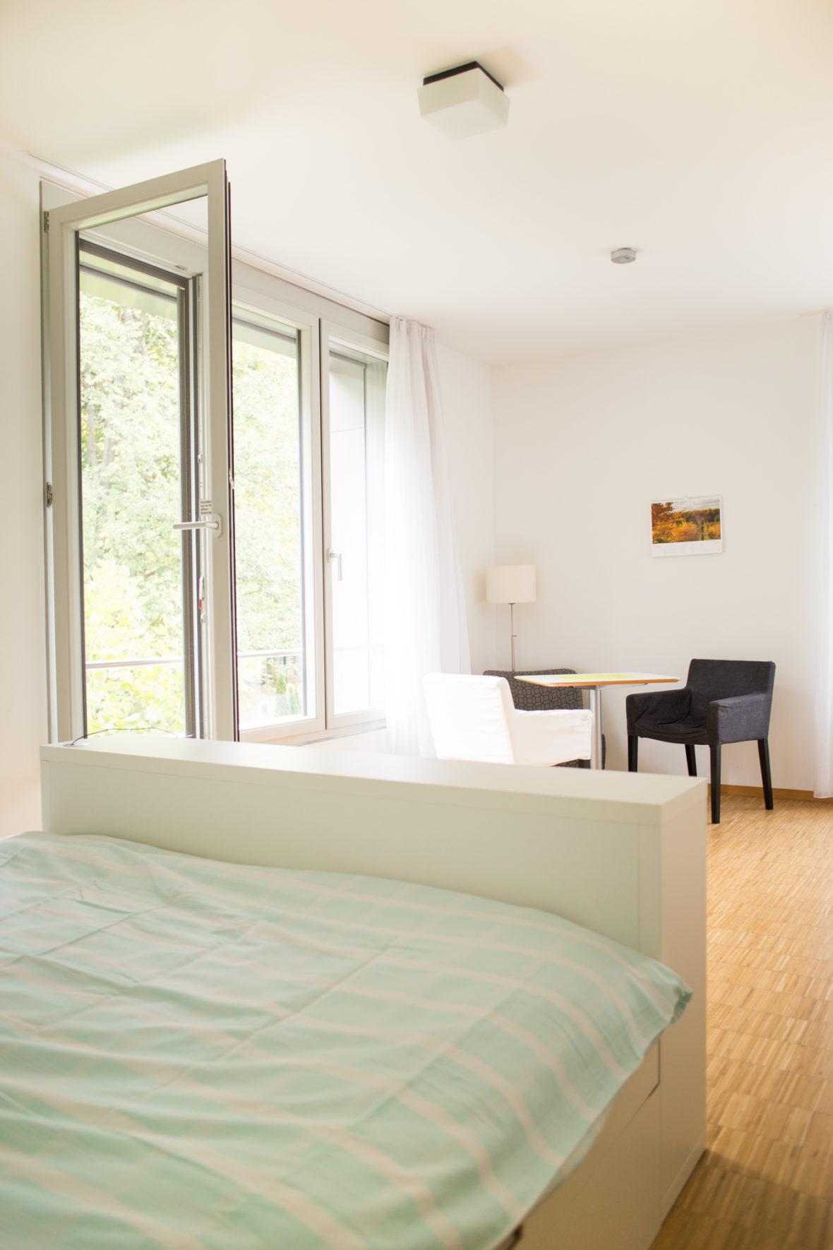 Die Zimmer sind hell und lichtdurchflutet: weiße Wände, ein weißes Doppelbett, heller Holzboden.