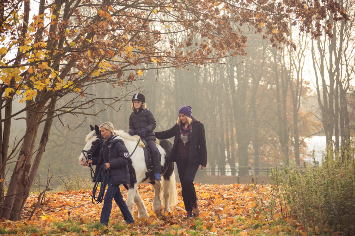 Mächold führt Maggy mit Alina auf dem Rücken über gelbes Herbstlaub. Alinas Mutter geht neben dem Pferd.