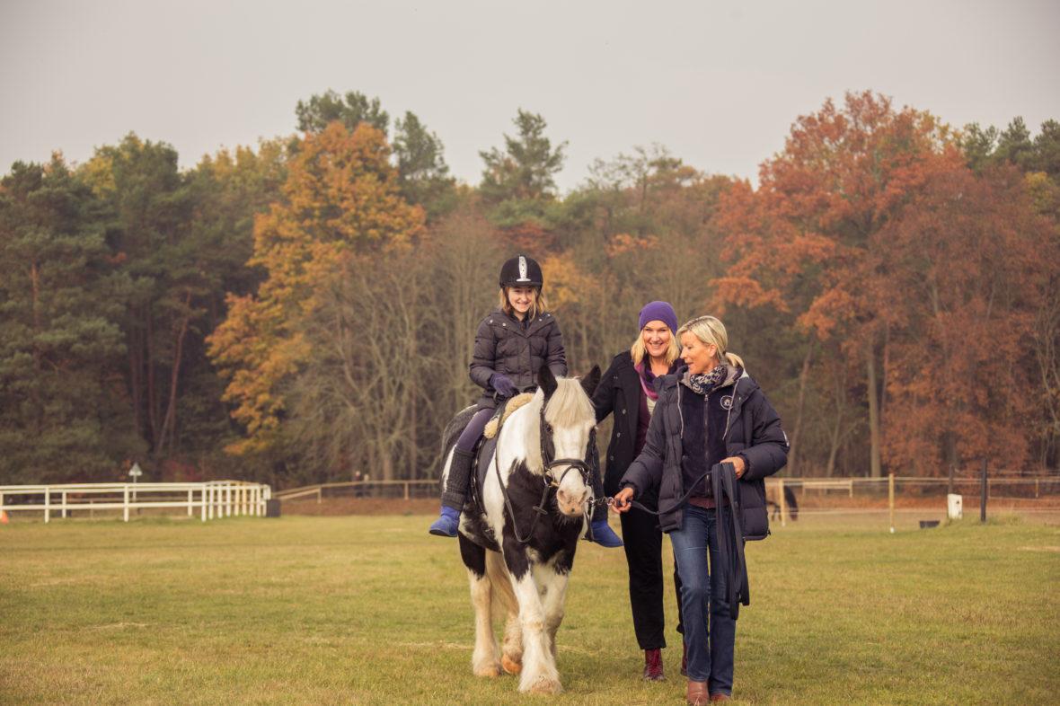 Mächold führt Maggy mit Alina auf dem Rücken über die Wiese. Alinas Mutter geht neben dem Pferd.