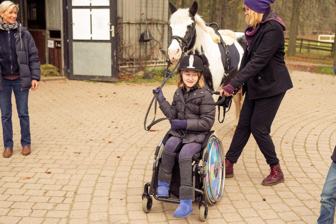 Alina sitzt im Rollstuhl und führt Maggy an einem Seil hinter sich her. Alina's Mutter schiebt den Rollstuhl vorwärts.