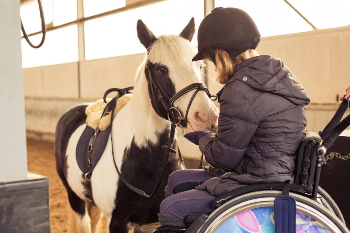 Alina sitzt auf einem Podest in ihrem Rollstuhl und streichelt die Nase von Maggy.