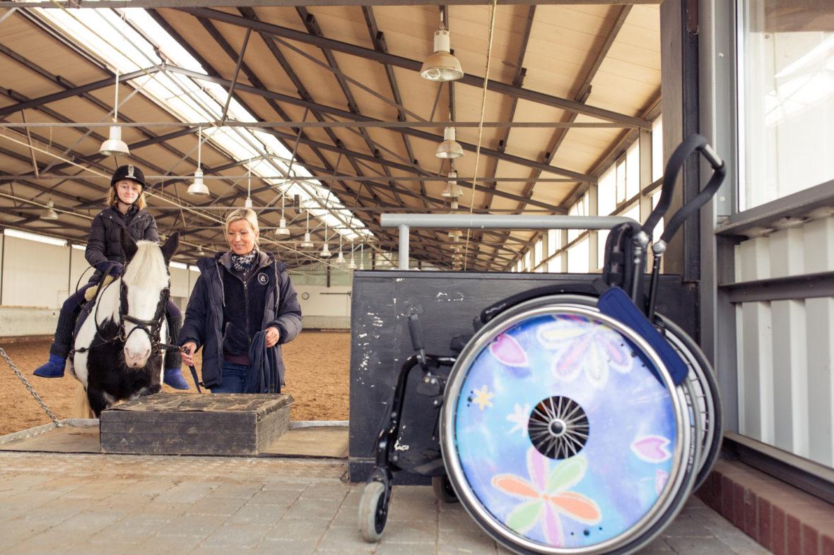 Mächold, Maggy und Alina im Reitstall. Im Vordergrund ist Alina's Rollstuhl zu sehen. Die Radabdeckungen sind bunt.