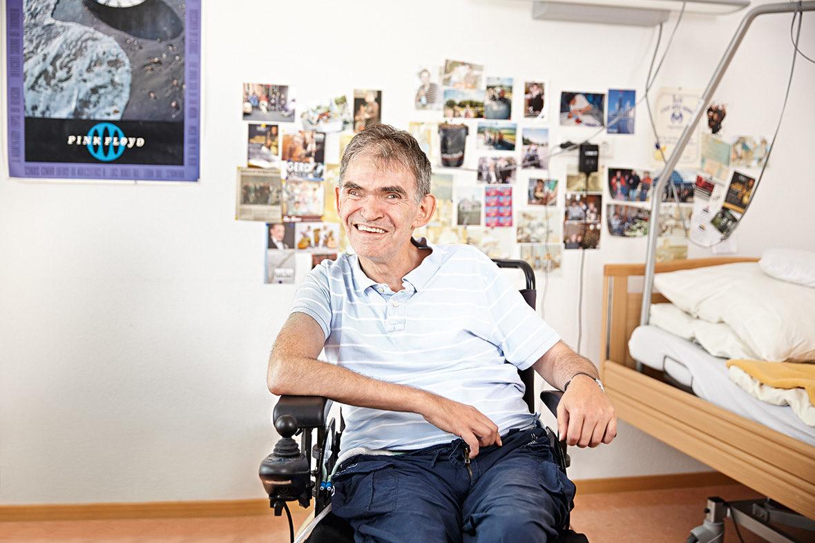 In seinem Zimmer sitzt ein Bewohner im Rollstuhl. Er lächelt in die Kamera.