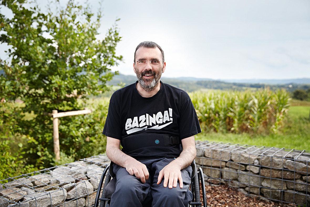 Ein Bewohner sitzt im Rollstuhl auf der Terrasse. Im Hintergrund sieht man die grüne Landschaft.