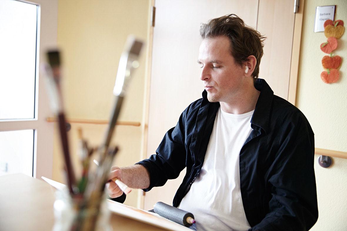Ein Bewohner sitzt an einem Tisch und malt. Im Vordergrund ist ein Glas mit Pinseln zu sehen.
