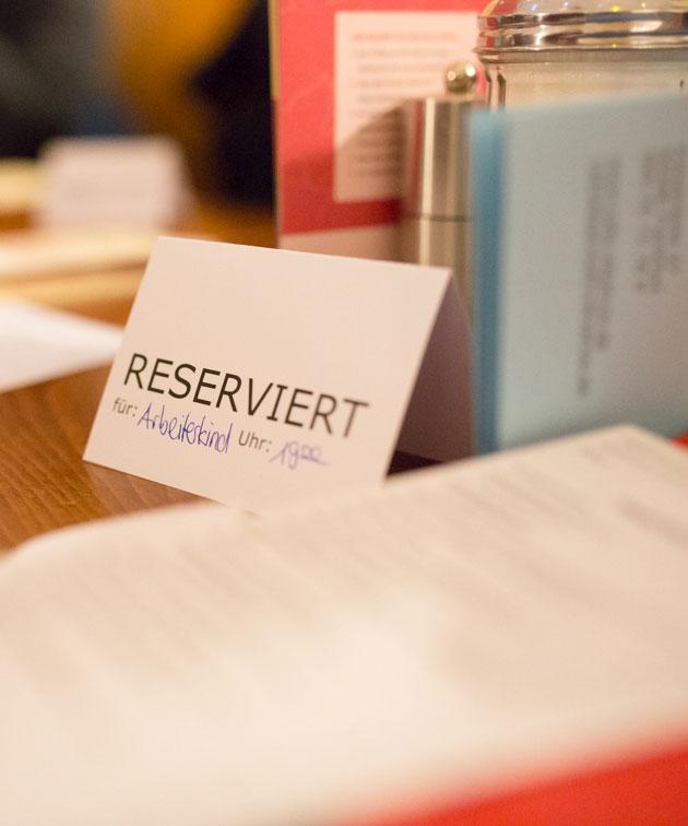 Ein Reserviert-Kärtchen auf einem Tisch, darauf steht: Arbeiterkind, 19 Uhr.