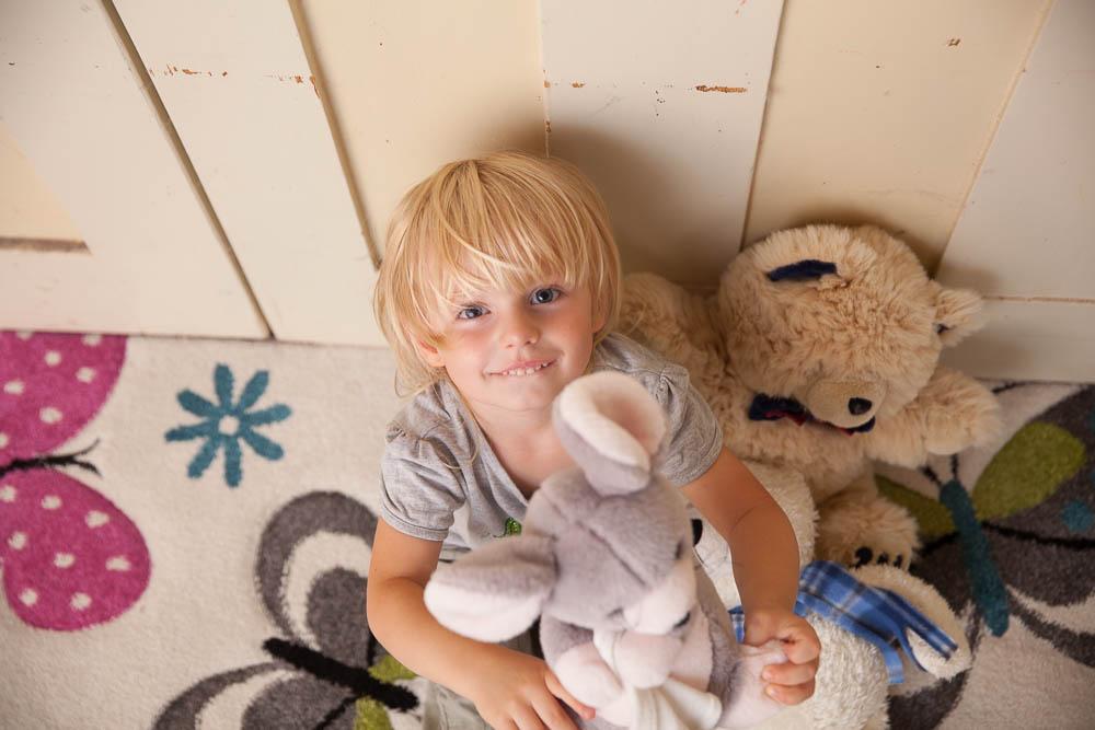 Ein kleiner blonder Junge sitzt auf einem bunten Teppich. Auf seinem Schoß sitzt eine graue Plüschmaus.