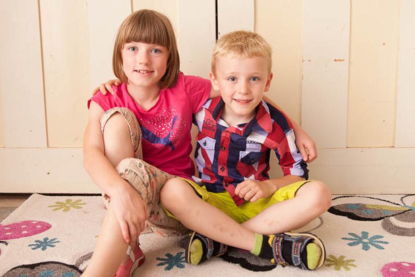 Ein braunhaariges Mädchen mit Pony und ein blonder Junge sitzen nebeneinander auf einem bunten Teppich. Sie legen sich gegenseitig den Arm um die Schulter und lachen in die Kamera.