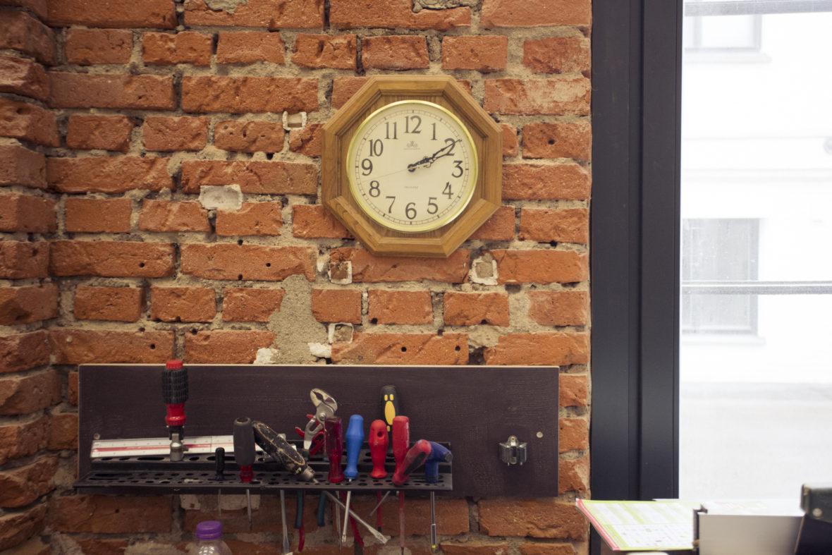 Eine Uhr zeigt zehn nach zwei am Nachmittag an. Darunter befinden sich vor einer unverputzten Backsteinmauer in der Werkstatt allerhand Schraubendreher, etwas chaotisch aufgehängt.