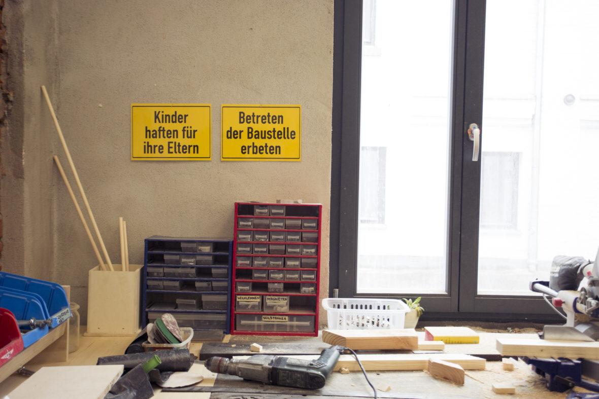 """Werkstatttisch: Darüber hängen zwei Schilder. """"Kinder haften für Ihre Eltern"""" und """"Betreten der Baustelle erbeten"""". Auf dem Tisch befinden sich Sortierkästen für Schrauben etc."""