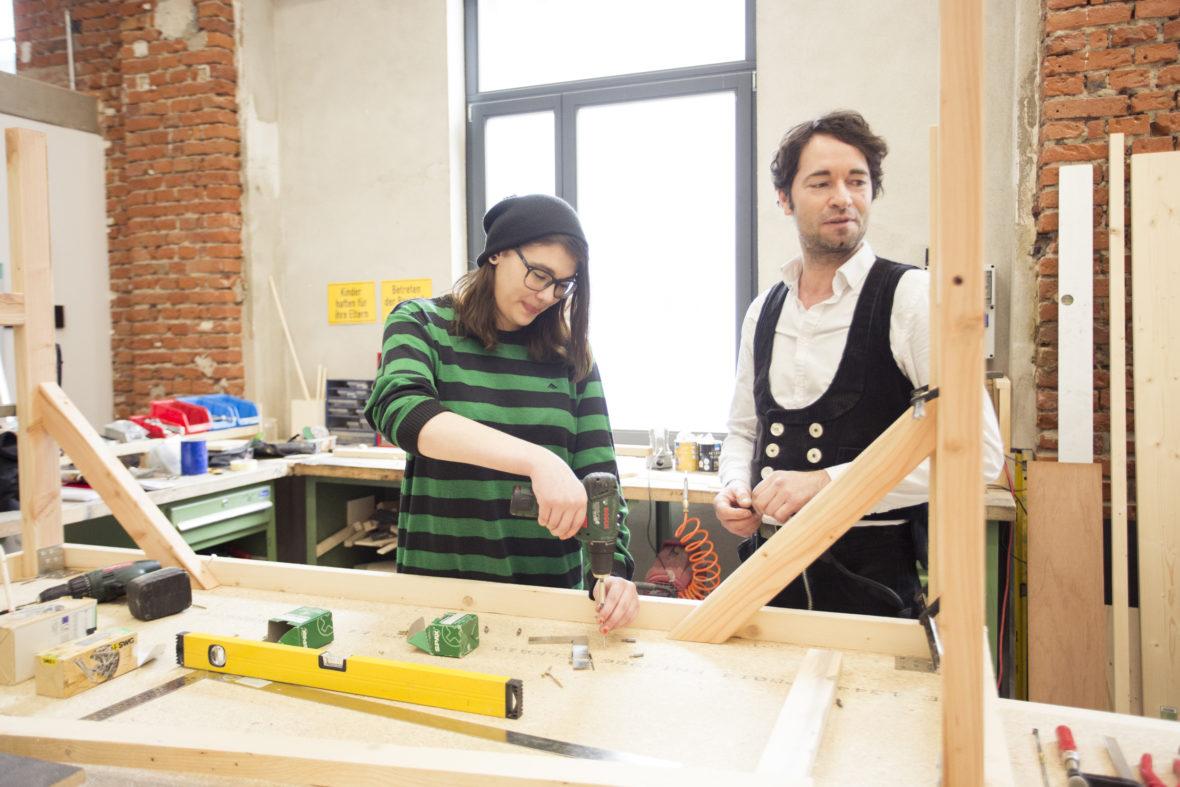 Vanessa arbeitet in der Werkstatt mit einem Bühnenbildner an einem Holzgerüst.