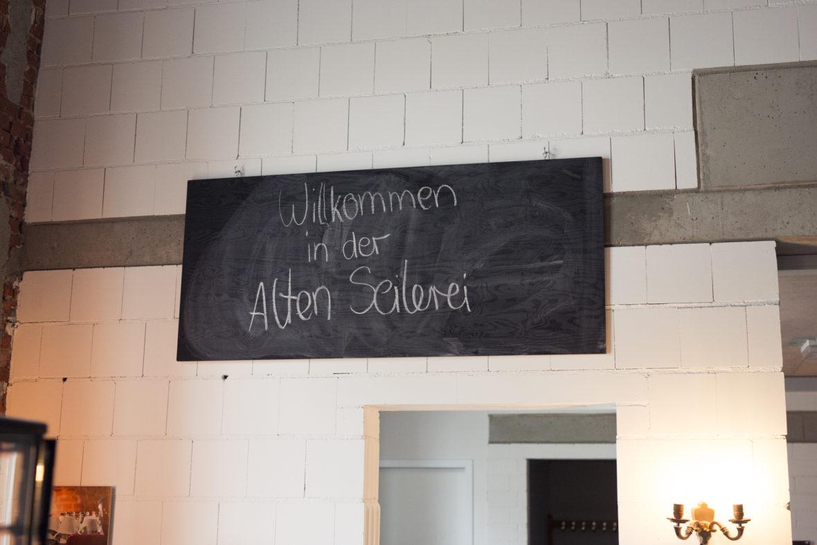 """Tafel über dem Barbereich mit der handgeschriebenen Aufschrift """"Willkommen in der alten Seilerei""""."""