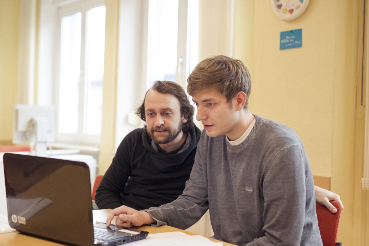 Denis arbeitet am Laptop an seiner Bewerbung zum Fachlageristen. Daniel Reichelt schaut ihm dabei über die Schulter.