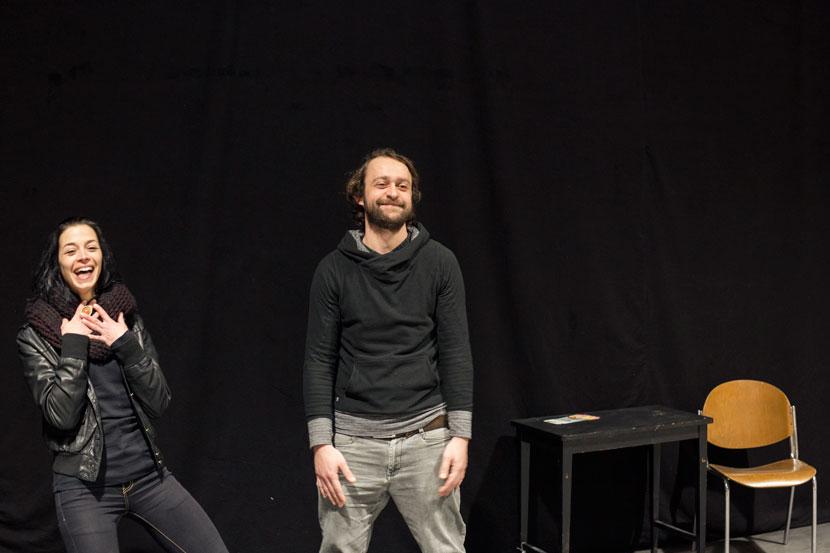 Eine junge Frau (links) und ein Mann stehen auf einer Bühne mit Tisch und Stuhl und lachen herzlich.