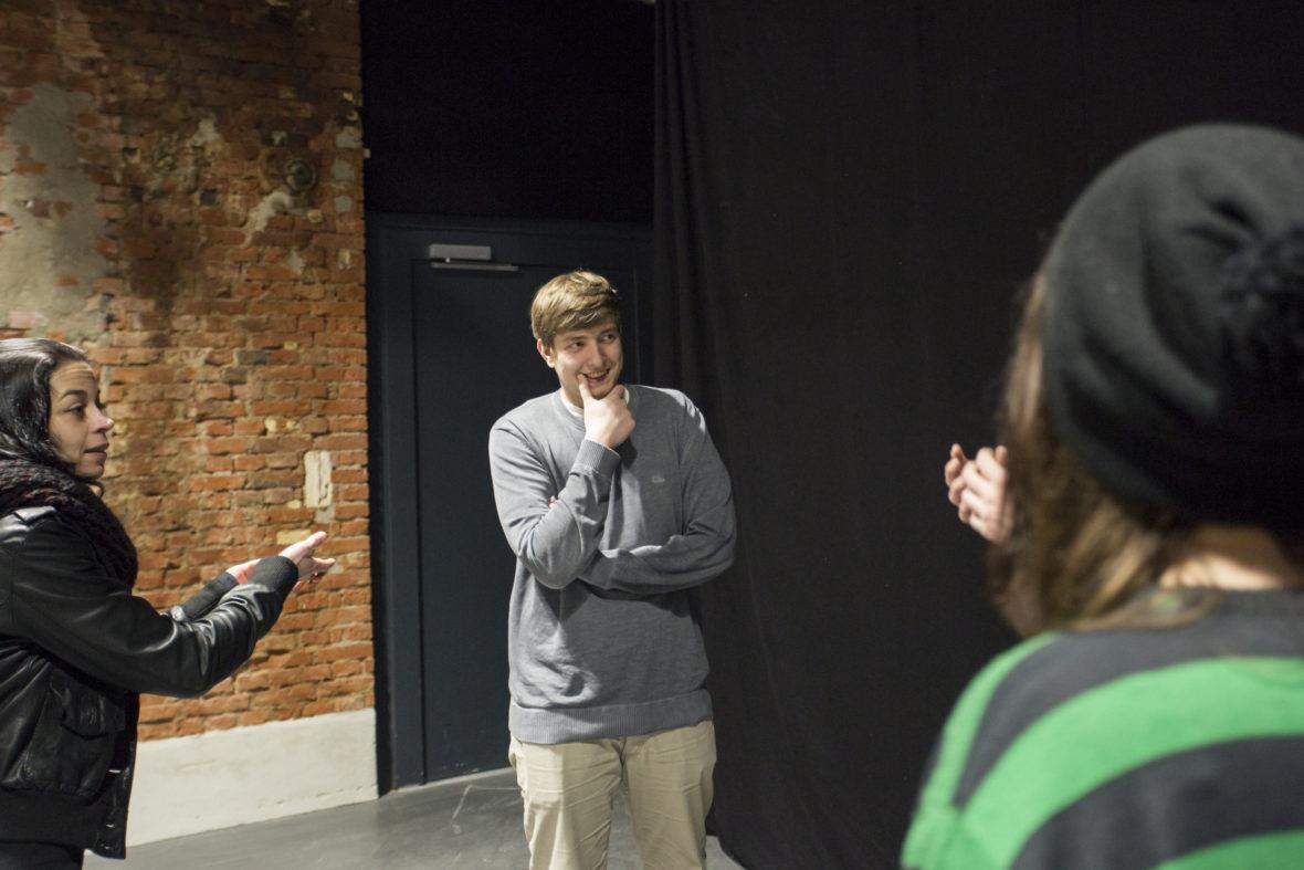 Theaterprobe: Zu sehen sind eine junge Frau (links), die eine auffordernde Handbewegung macht. Ein junger Mann steht im Zentrum und schmunzelt.
