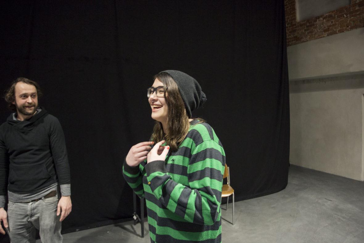 Eine Junge Frau lacht, als sie bei einer Theaterprobe eine Mimik-Übung macht. Ihr Betreuer sieht zu