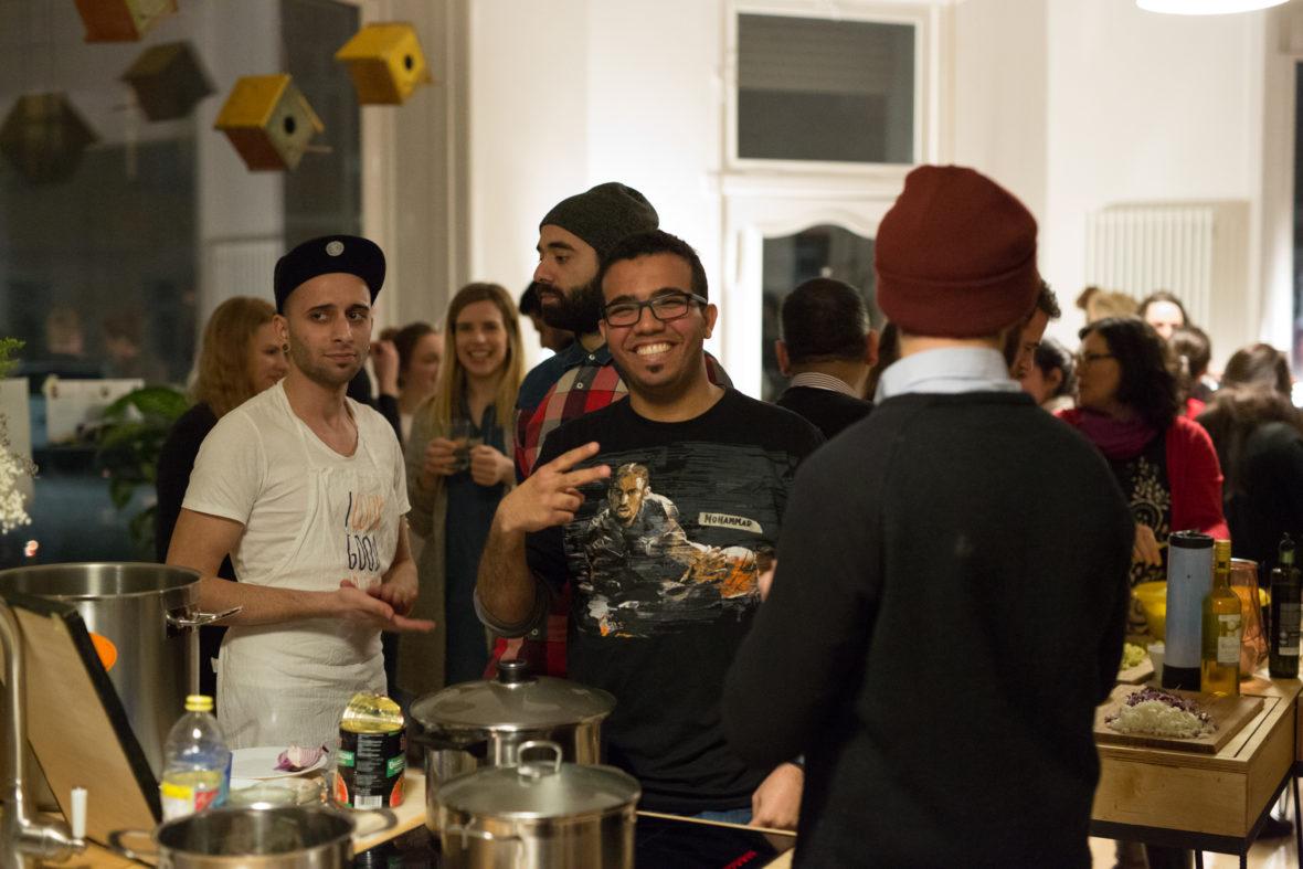 Mohammad steht lachend am Kochtopf und zeigt mit seinen Fingern das Peace-Zeichen.